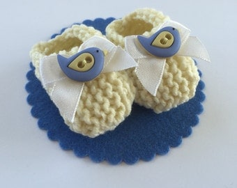 CAKE TOPPER baby shower decorations: hand knit light yellow mini booties, white bow, blue yellow bird buttons, felt base - 2 inches