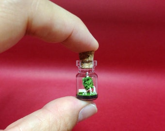 Tiny green tree and a couple and baby in a tiny bottle.