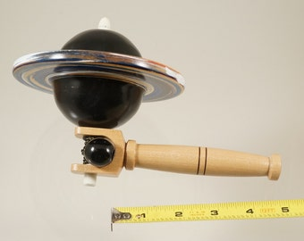 Toy top. Wood spinning top with handle. Black Hole top.