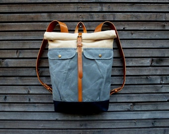 Waxed canvas backpack with roll to close top and vegetable tanned leather shoulderstrap and back reinforcement