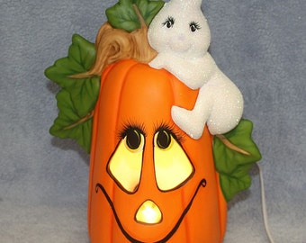 Handpainted Ceramic Little Ghost Climbing on a Pumpkin with a Jack O Lantern Face and Light