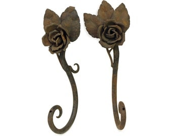 Pair of worn floral curtain hooks