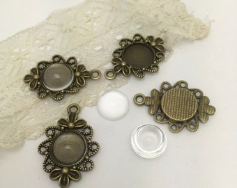 4 ornate bezel in  antique  bronze .Holds  12 mm cabochons and comes with 4 clear 12 mm cabochons