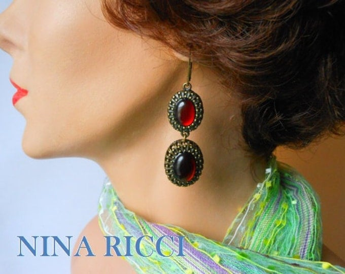 Nina Ricci earrings, dangling opaque red oval cabochons framed in ornate bronze colored metal, lever back earrings, free swinging