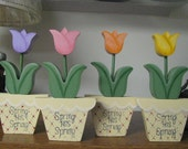 Spring has sprung written on flower pot, shelf sitter, pink, purple, yellow, peach