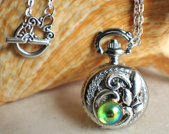 Pocket watch locket with peridot green glass cabochon and silver accents on front cover.
