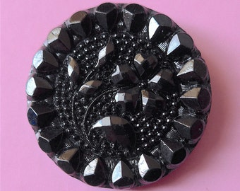 Black glass button, antique.   It has a central floral design, a dotted background, & a decorative border, metal loop shank. c1900-1910's.