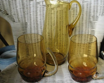 Pitcher and 2 cups amber cast glass.