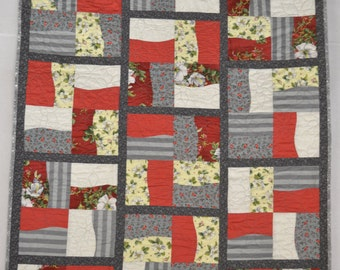 Quilted wall hanging or lap quilt. Machine pieced and quilted red, gray, and off-white fabrics with free motion flowers quilting