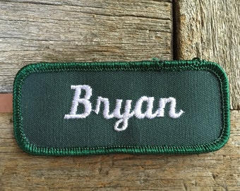 "Bryan - LAST ONE! A green work shirt name patch that says ""Bryan"" in white script"