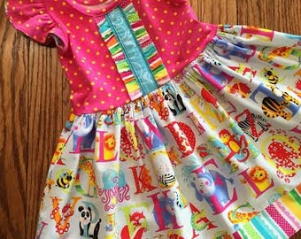 Alphabet Zoo, blue or pink bodice.  Perfect for back to school. Bodice is a soft Euro knit with a nice 4 way stretch. Zoo animals. Sz 12mo-8