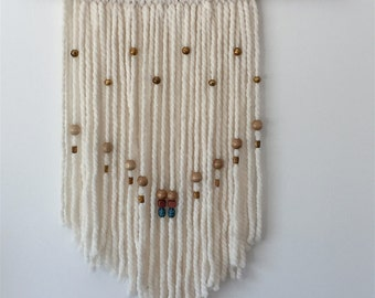 Wall weave art. Handmade in Santa Fe and inspired by the Southwest. White in color with decorative beading. Measures 13inx24in.