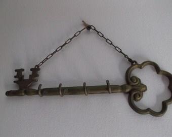 Wall key holder in brass, key-shaped