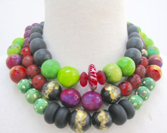 triple strand, short necklace, hand painted wood beads, purples,greens,blacks, reds. Light weight. Wonderful colors.