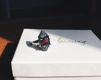 Sterling silver ring with a garnet stone and marcasites