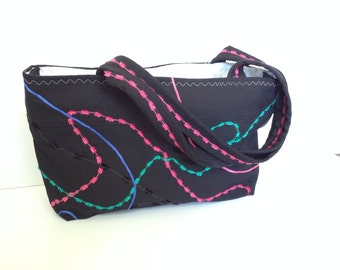 Black upcycled purse with bright pink and teal embellishment