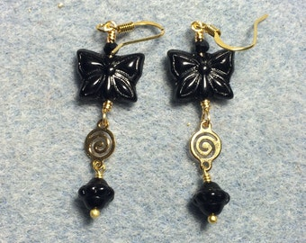 Black Czech glass butterfly bead dangle earrings adorned with gold swirly connectors and black Saturn beads.