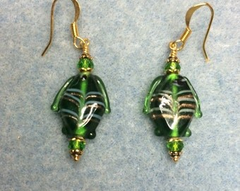 Green transparent lampwork fish bead dangle earrings adorned with green crystal beads.