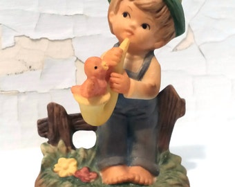 Figurine Boy Sitting on Fence Playing his Saxophone Hand Painted Porcelain