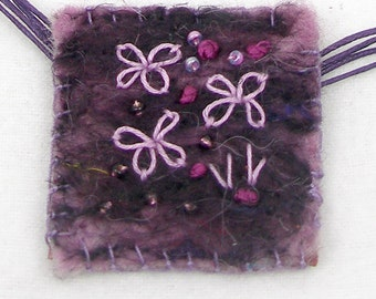 Pendant made from felt with stitch and beads added. Tiny landscape or floral scene specially to wear.