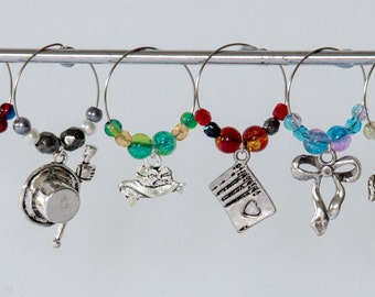 6 Jane Austen themed wine glass charms, including a soldier, top hat, bonnet, playing cards, ribbon and a Chaise.