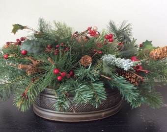 Christmas tabletop centerpiece with greenery,berries and pinecones