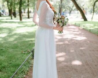 Elegant wedding dress of ivory color, floor length, A-line shape, long netting sleeve, semi-open back, wedding gown