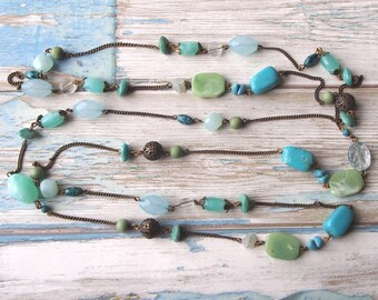 Lovely long vintage bead necklace with light blue, green, clear and bronze tone beads