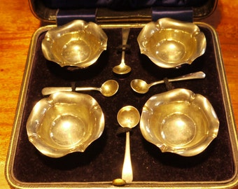 Antique cased set of four Edwardian silver open salts together with four spoons by Flavelle brothers