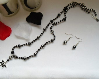 Long black and silver coloured dragonfly necklace and earring set