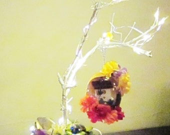 White tree hanger, twinkle lights, decorated moss covered base, bead turtle, carved egg with miniature birdhouse theme.