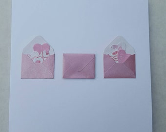 Handmade greetings card with envelope and heart embellishments.