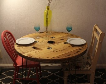 A rustic cable reel dining table with steel hairpin legs
