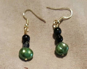 Green pearls with black beads dangle earrings