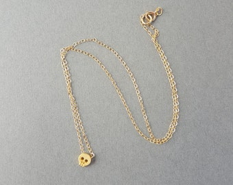 Tiny gold skull charm necklace