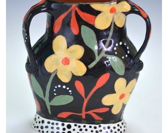 Small Black Vase with Yellow flowers and foliage.