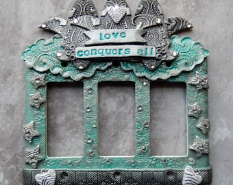 Love Conquers All, triple rocker light switch cover, polymer clay with rhinestones and glitter in gray, silver, light aqua and white