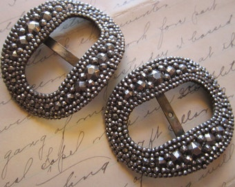 2 antique steel cut buckles - oval, cut steels