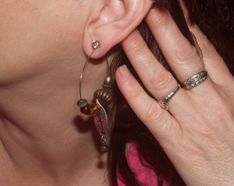 Silver-tone oval earrings w/ brass-tone and glass beads, and silver-tone leaf w/ wood bead suspended.