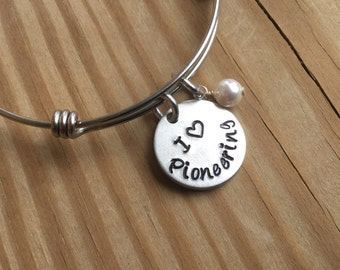 """JW Pioneering Bracelet- Hand-Stamped """"I (heart) Pioneering"""" Bracelet with an accent bead in your choice of colors"""