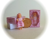Molly Dolly, dolls house miniature toy doll in a box, wearing pink. A dolly for your dolls house doll.