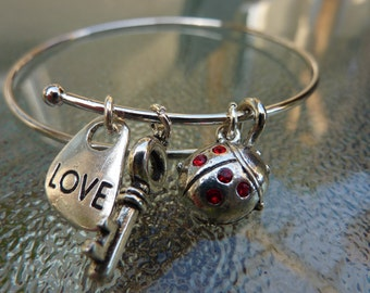 Bangle:silver plated adjustable bangle with SWarovski elements lady bug,key and love charms