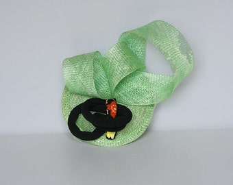 Green and black  fascinator on base with comb.