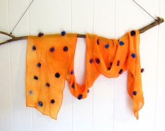 Orange silk scarf with purple and blue wool pom poms, twilight colors, sunset.