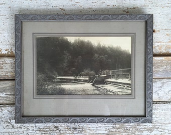 Antique gray carved wood frame with black white photo of wooden dam