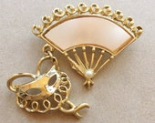 vintage gold tone metal fan shaped brooch with dangling party mask charm and mother of pearl inlay