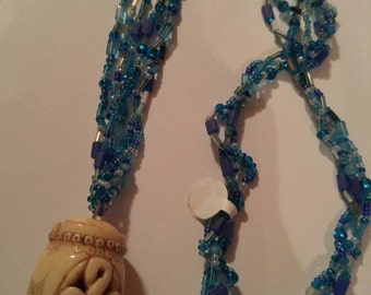 Beaded necklace with carved bone pendant