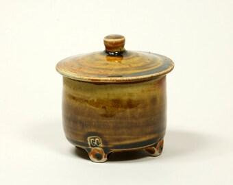 Salt fired amber glazed porcelain lidded pot with 4 feet