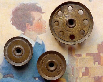 Meccano wheels, 3, vintage.  Old pieces of Meccano, l large brass wheel and 2 small.  c 1920's.