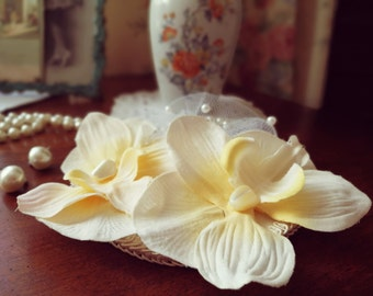 Cream and white fascinator with two orchids and pearls